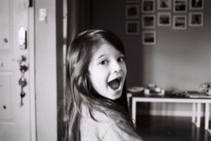 Black and white image of a girl laughing - 5 Film Cameras Under 50 Dollars by Jennifer Stamps on Shoot It With Film