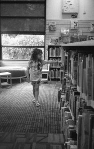 Black and white image of girl in library - 5 Film Cameras Under 50 Dollars by Jennifer Stamps on Shoot It With Film