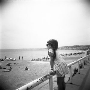 Black and white film image of a girl looking over a railing at the beach - 5 Film Cameras Under 50 Dollars by Jennifer Stamps on Shoot It With Film