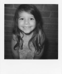Black and white Polaroid picture of a girl smiling - 5 Film Cameras Under 50 Dollars by Jennifer Stamps on Shoot It With Film