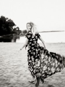 Black and white image of a woman running down the beach in a flowy dress - 6 Film Photography Tips for Beginners by Samantha Stortecky on Shoot It With Film