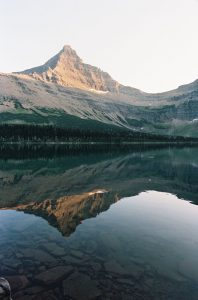 Mountains reflected in a lake photographed on 35mm film - Glacier National Park Travel Story by Jill Bridgeman on Shoot It With Film