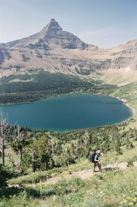 Landscape of a lake at the base of a mountain photographed on 35mm film - Glacier National Park Travel Story by Jill Bridgeman on Shoot It With Film