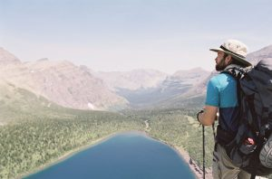 Man hiking with a view of the mountains and a lake photographed on 35mm film - Glacier National Park Travel Story by Jill Bridgeman on Shoot It With Film