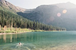 A lake surrounded by mountains photographed on 35mm film - Glacier National Park Travel Story by Jill Bridgeman on Shoot It With Film
