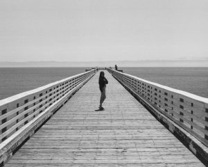 Black and white image of a woman on a long pier on Ilford Delta 3200 film - Guide to Ilford BW Film by David Rose on Shoot It With Film