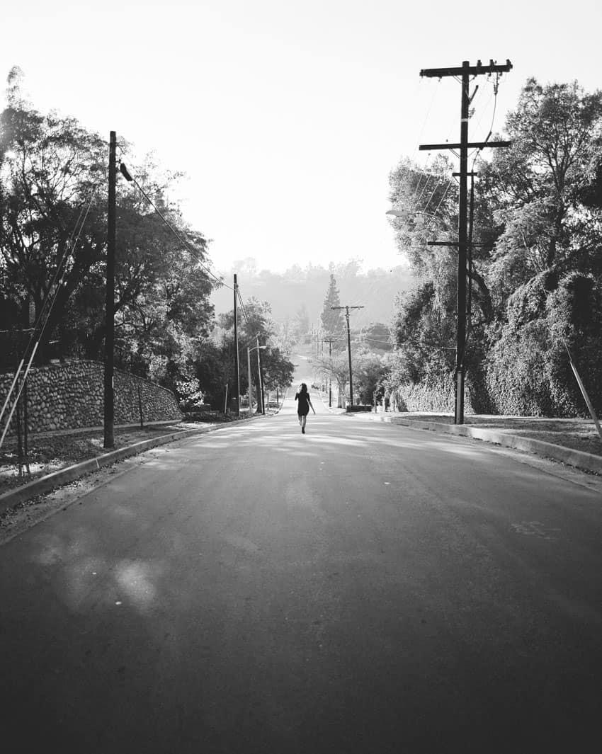 Черно-белое изображение женщины, стоящей в центре дороги, на фильме Илфорд XP2 - Путеводитель по фильму Илфорд BW Дэвида Роуза на тему «Снимай с пленки»