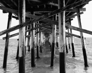 Black and white image of beams under a pier on Ilford FP4 film - Guide to Ilford BW Film by David Rose on Shoot It With Film