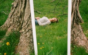 Reflection in a mirror of a woman laying on the grass - The Seed I Nurtured Fine Art Series by Chloe Xiang on Shoot It With Film