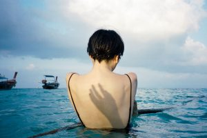 35mm film image of a shadow of a hand on a woman's back in the ocean - Fine Art Series by Nick Prideaux on Shoot It With Film