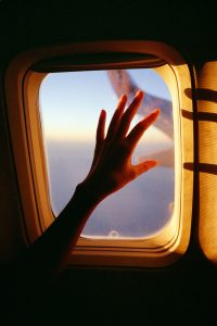 35mm film image of a hand on an airplane window - Fine Art Series by Nick Prideaux on Shoot It With Film