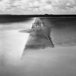 Black and white film photography long exposure of a concrete divider in the water - Understanding Reciprocity Failure in Long Exposure Film Photography by James Baturin on Shoot It With Film