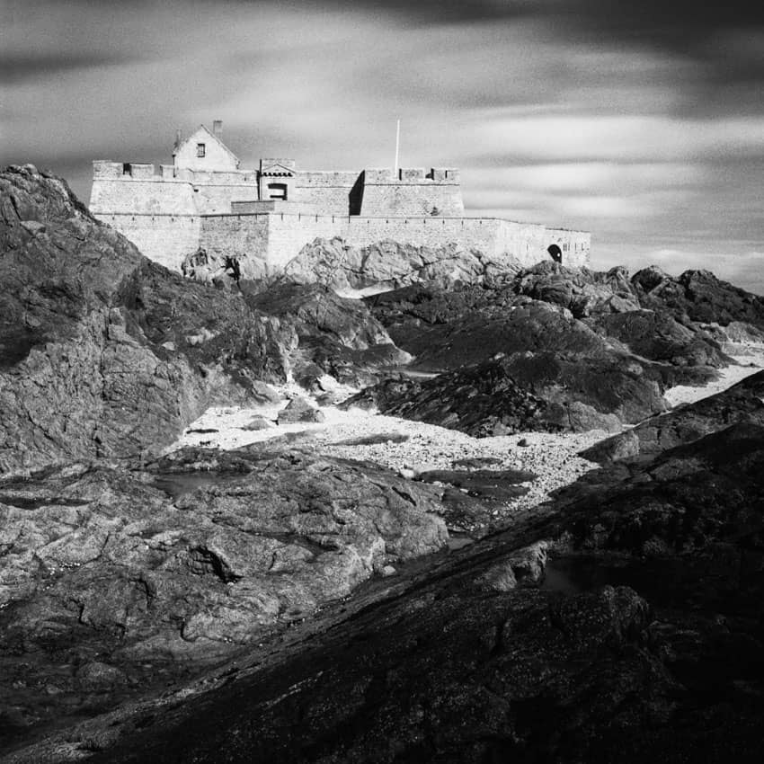 Black and white film photography long exposure of a castle on the coast - Understanding Reciprocity Failure in Long Exposure Film Photography by James Baturin on Shoot It With Film
