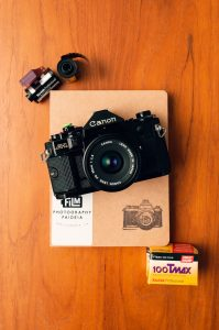 Film camera on top of a notebook - 10 Awesome Gifts for Film Photographers on Shoot It With Film
