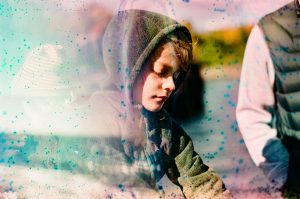 35mm film photography image using a prism and film soup of a boy sitting by a river - 5 Creative Film Photography Projects to Try When You're Uninspired by Amy Berge on Shoot It With Film