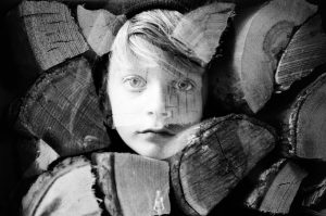 35mm film photography double exposure black and white image of a boy and firewood - 5 Creative Film Photography Projects to Try When You're Uninspired by Amy Berge on Shoot It With Film