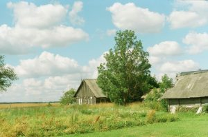 Grassy field with a barn on 35mm film - Eastern Europe Travel Story by Taylor Stoker on Shoot It With Film