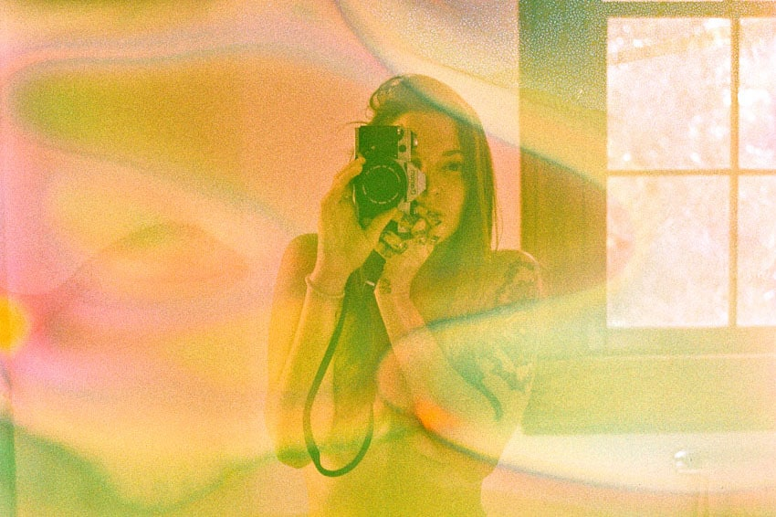 35mm film self portrait of a woman holding a camera made with film soup - Stained Film Self Portraits by Anna Gibbs on Shoot It With Film