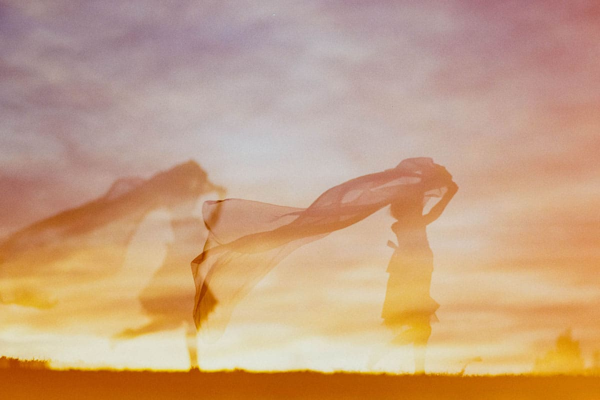 Film double exposure of a girl running through a field
