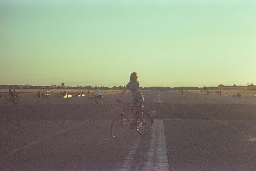 35mm film image of a woman riding a bike - Berlin Travel Story by Carolina Nobile on Shoot It With Film